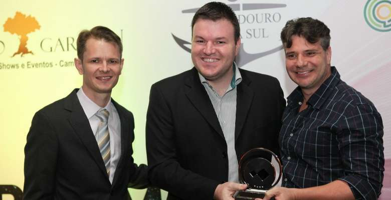 Augusto Munchen e Rodrigo Escobar, da Diretoria da Acibalc, entregando o prêmio para Rodrigo Cacheta, da Schultz Massa